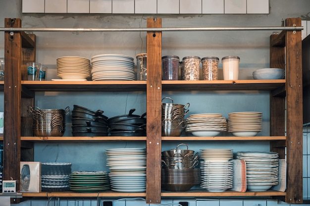 Naczynia kuchenne z naczyniami trzymane na drewnianych półkach kuchennych