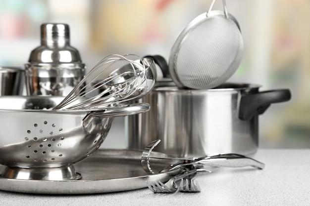 Naczynia kuchenne ze stali nierdzewnej na stole, oświetlone