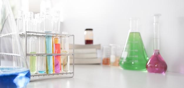 Naczynia laboratoryjne zawierające kolorowe ciecze nakładane na stół.