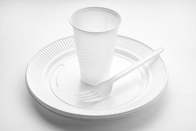 Naczynia plastikowe. biały wazon, talerz i widelec na białym tle. jednorazowe odpady z tworzyw sztucznych