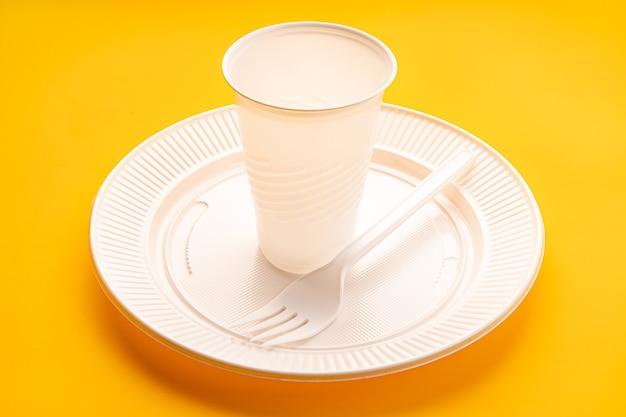 Naczynia plastikowe. biały wazon, talerz i widelec na żółtym tle. jednorazowe odpady z tworzyw sztucznych