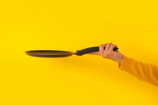 Naczynie do naleśników w ręku na żółtym tle