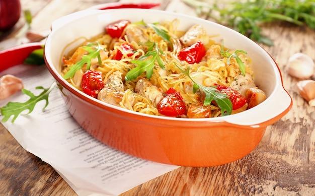 Naczynie do pieczenia z pysznym spaghetti z kurczaka na stole
