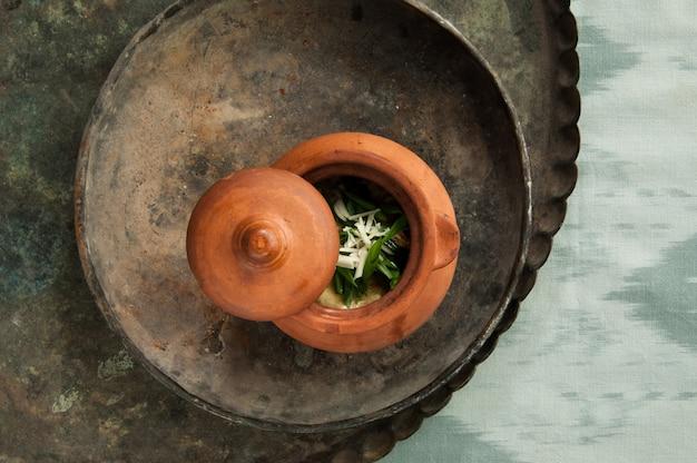 Naczynie w glinianym garnku na starej antycznej tacy