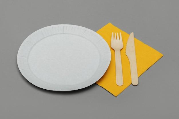 Naczynie z białego papieru, drewniany widelec i nóż i żółte serwetki na szarym tle. zestaw ekologicznych naczyń jednorazowych z naturalnego materiału. koncepcja ekologiczna.