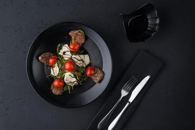 Naczynie z grillowanego mięsa na czarnej drewnianej powierzchni, widok z góry