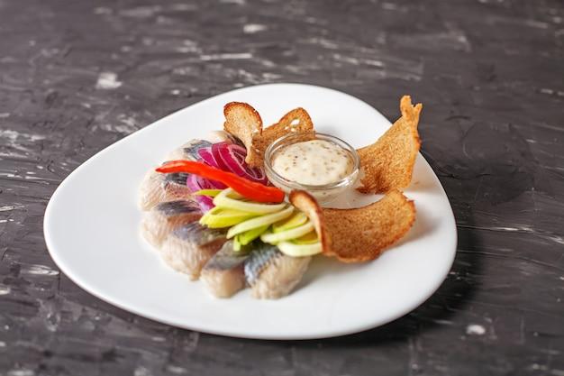 Naczynie z śledziem na białym talerzu. pojęcie żywności, restaur