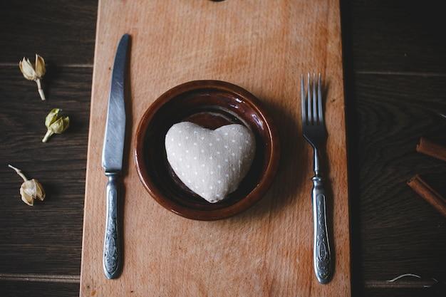 Naczynie z sztućcami i kształcie serca wewnątrz