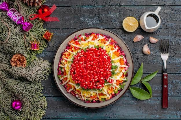 Naczynie z widokiem z góry i gałązki świerkowe apetyczne danie świąteczne z olejkiem cytrynowym obok widelca gałązki świerkowe z szyszkami