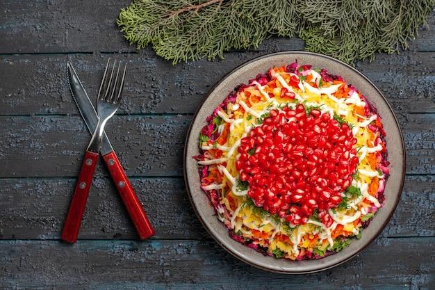 Naczynie z widokiem z góry i gałązki świerkowe naczynie świąteczne obok noża i widelca gałązki świerkowe na ciemnym stole