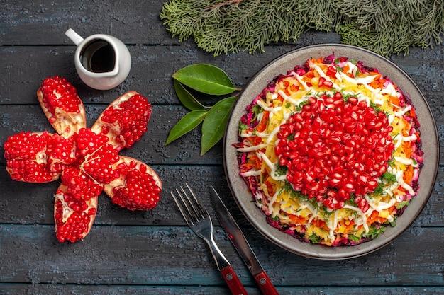 Naczynie z widokiem z góry i gałązki świerkowe świąteczne naczynie zasypane olejem z granatów obok noża i widelca gałązek świerkowych na ciemnym stole