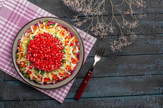 Naczynie z widokiem z góry i talerz widelca z apetycznym daniem na obrusie obok gałęzi drzew i widelec na szarym stole