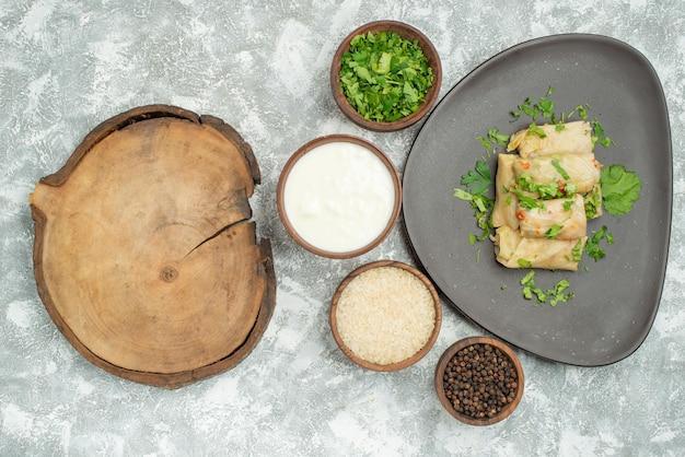 Naczynie z widokiem z góry z talerzem ziół z gołąbkami obok drewnianej deski do krojenia i miskami ziół z kwaśną śmietaną, ryżem i czarnym pieprzem na stole