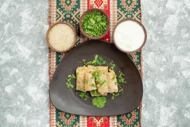 Naczynie z widokiem z góry z ziołami szara miska z gołąbkami kapusty ziołami kwaśną śmietaną ryż na kolorowym obrusie z wzorami na środku stołu