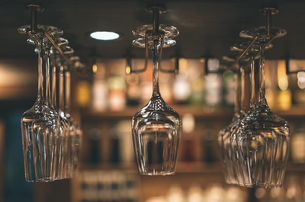 Nad barem zawieszone są szklanki do napojów alkoholowych.
