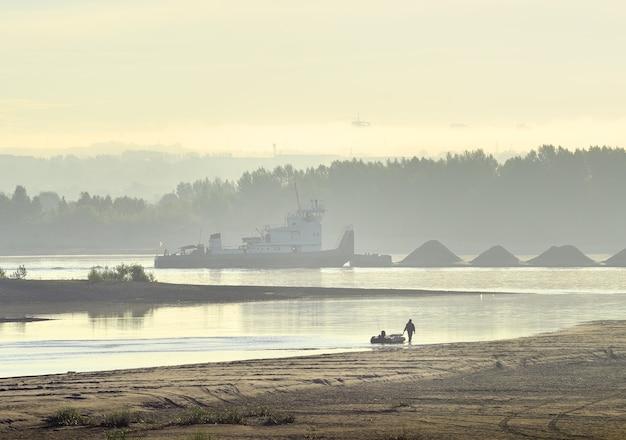 Nad brzegiem obu spaceruje rybak. barka towarowa płynie przez poranną mgłę
