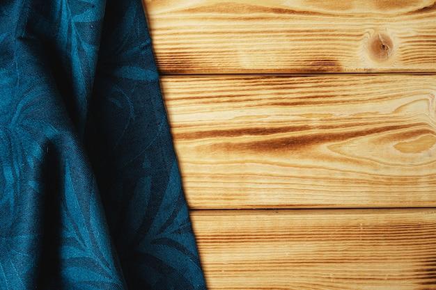 Nad drewnianym stołem ręcznik kuchenny lub serwetka.