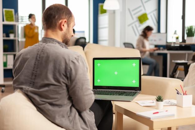 Nad głową menedżera siedzącego na kanapie, trzymającego laptopa z zielonym ekranem, makiety pulpitu, podczas gdy zróżnicowany zespół pracuje w tle