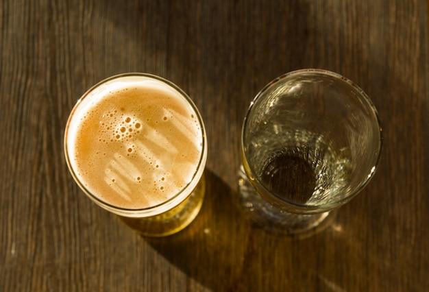 Nad głową szklankę piwa obok pustej szklanki na drewnianym stole