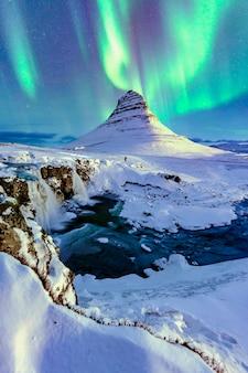 Nad górą kirkjufell na islandii pojawia się zorza polarna