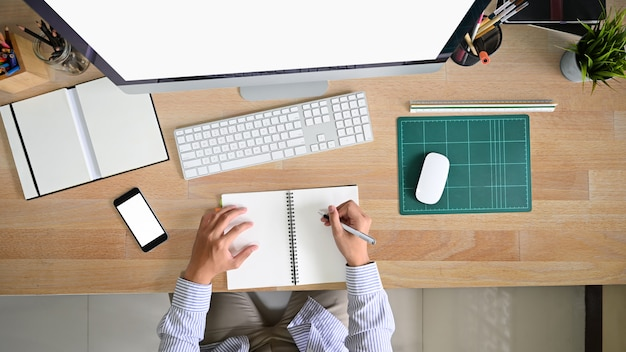 Nad headshot młody człowiek pracuje na biurowym obszarze roboczym z drewnianym stołem.