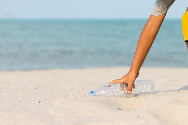 Nad morzem mały chłopiec podnosi plastikową butelkę na plaży i wyrzuca ją do kosza.