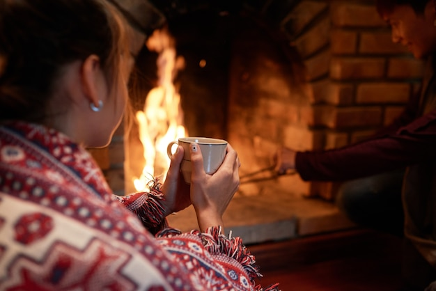Nad ramieniem ujęcie kobiety rozgrzewającej ręce na kubku gorącej herbaty siedzącej przy kominku, jej chłopak zajmujący się węglem drzewnym