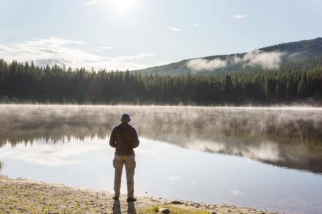 Nad spokojnym jeziorem odpoczywa człowiek. pobyt relaksacyjny