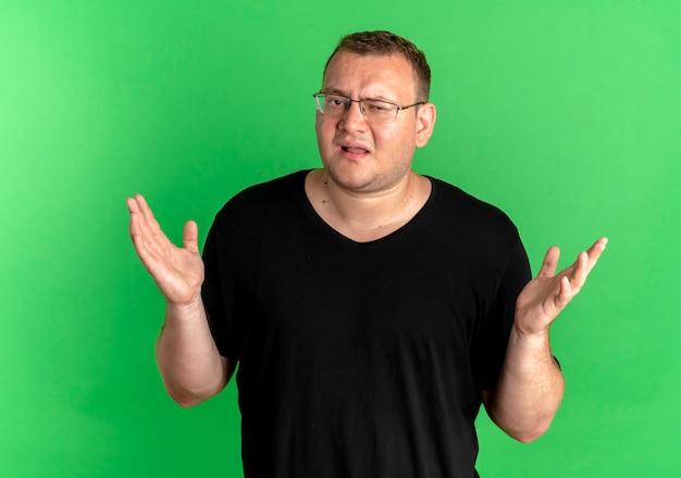 Nad zieloną ścianą mężczyzna z nadwagą w okularach i czarnym t-shircie wygląda na zdezorientowanego, wzruszając ramionami