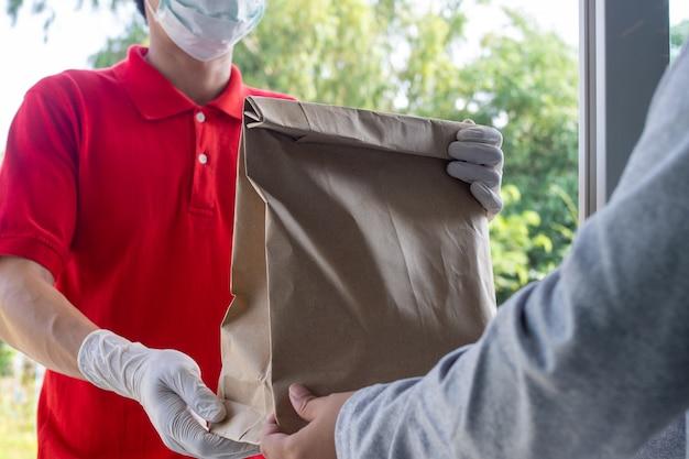 Nadawca nosi maskę i rękawiczki, dostarczając żywność do domu kupującego online. pozostań w domu, aby ograniczyć rozprzestrzenianie się wirusa covid-19. nadawca ma możliwość szybkiego dostarczenia produktów lub żywności