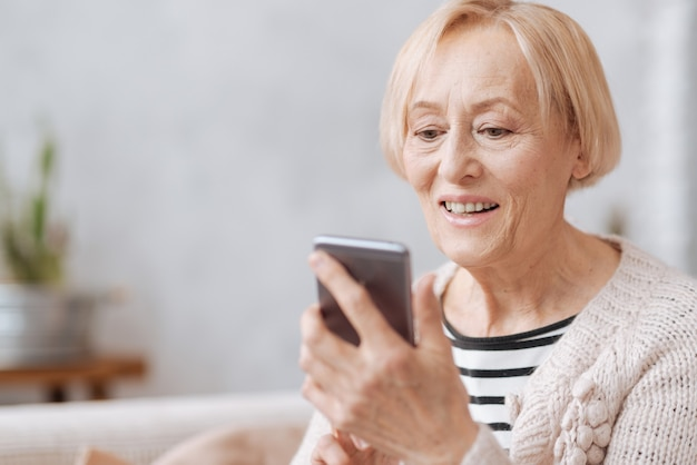 Nadążamy za czasem. uśmiechnięta przyjazna starsza pani, trzymając smartfon w dłoniach i wpisując coś, spędzając czas w domu
