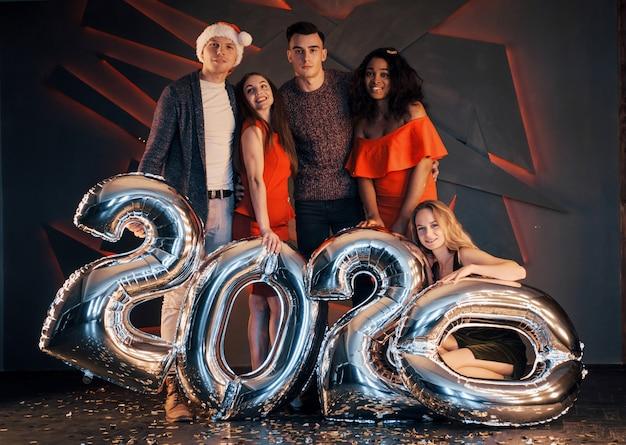 Nadchodzi nowy rok 2020. grupa zabawy młodych ludzi międzynarodowych na imprezie. szczęśliwego nowego roku