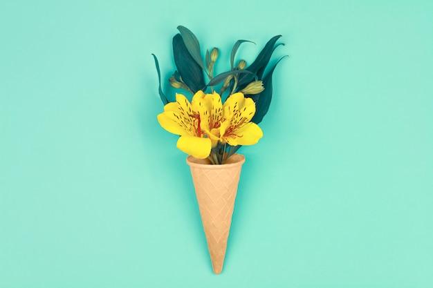 Nadchodzi wiosna. bukiet żółtych kwiatów z zielonymi liśćmi w rożkach waflowych