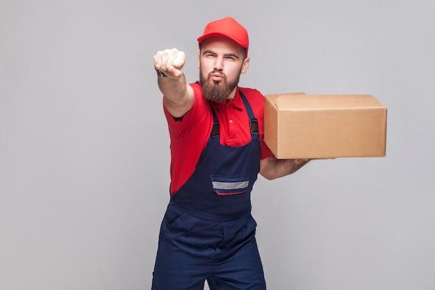 Nadczłowiek! młody w pośpiechu logistycznym człowiek dostawy z brodą w niebieskim mundurze i stojącej czerwonej koszulce, trzymając karton na szarym tle. wewnątrz, studio strzał, odosobniona, kopia przestrzeń