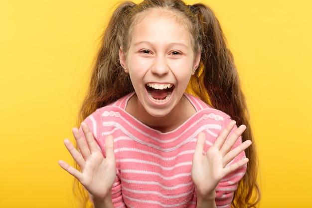 Nadmiernie podekscytowana, entuzjastyczna roześmiana dziewczyna. portret dziecka na żółto. emocje i wyraz twarzy.