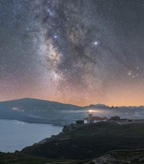 Nadmorski krajobraz nocą z morzem i drogą mleczną na niebie i latarnią morską świecącą w świetle