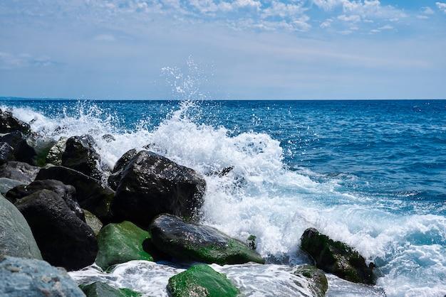 Nadmorski krajobraz z ciepłym wieczornym światłem, kiedy fale rozbijają się o skały pokryte wodorostami