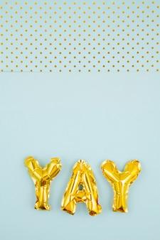 Nadmuchane litery przebijają pastelowe tło ze złotymi kropkami. impreza, uroczystości, święta