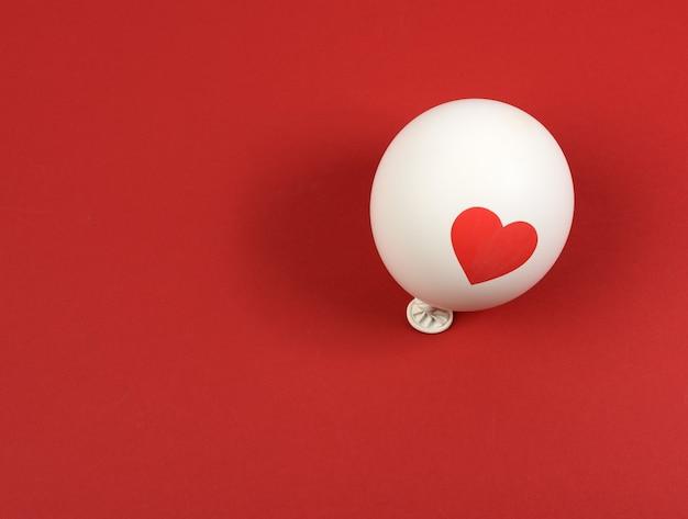 Nadmuchany biały balon na czerwonej powierzchni, widok z góry