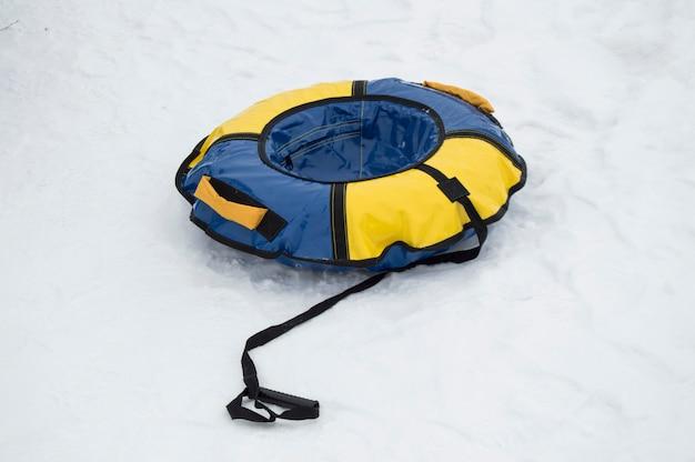 Nadmuchiwane gumowe rurki w kolorze niebieskim i żółtym do jazdy na nartach w zimie ze zjeżdżalniami na śniegu