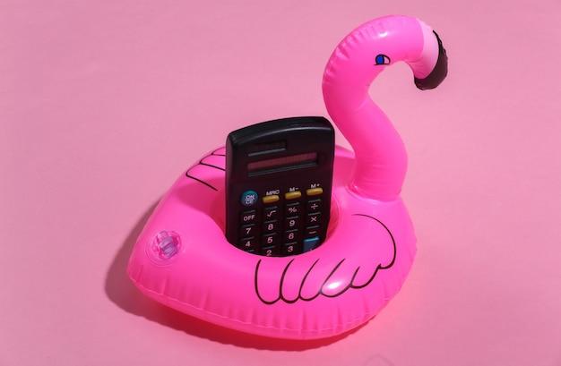 Nadmuchiwane różowe flamingi i kalkulator na różowym słonecznym tle. koncepcja wakacji letnich. minimalizm