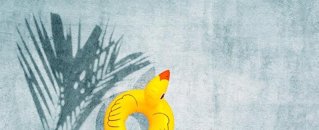 Nadmuchiwane żółtej kaczki z tropikalną palmą pozostawia cień na betonowym tle. letnia koncepcja tła