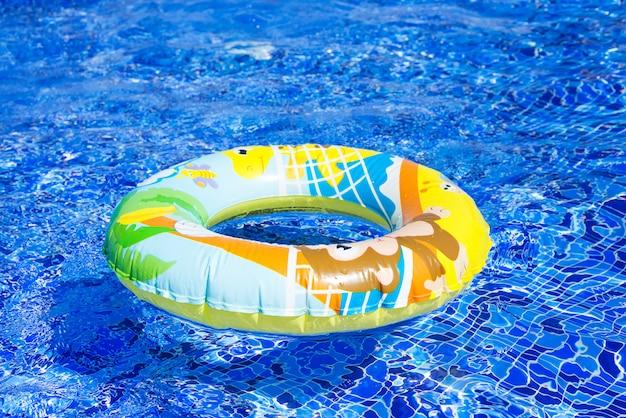 Nadmuchiwany kolorowy pierścionek unosi się w basenie w słoneczny dzień
