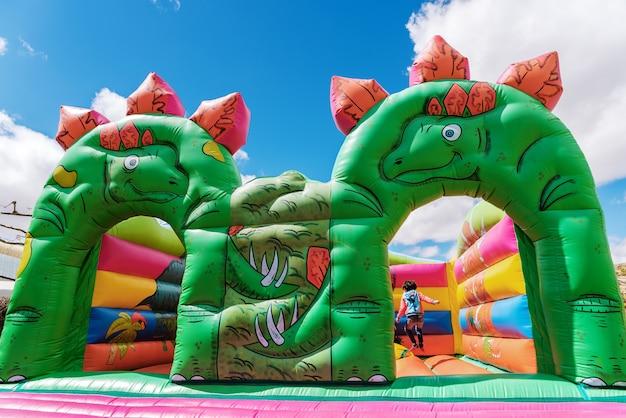 Nadmuchiwany zamek w kształcie dinozaurów na placu zabaw dla dzieci na świeżym powietrzu.