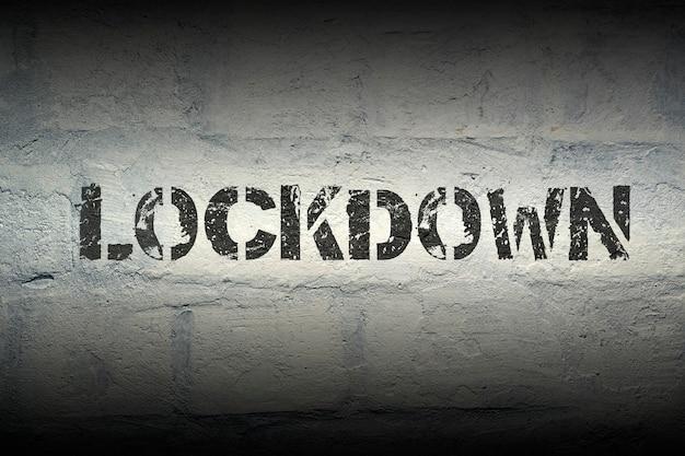Nadruk szablonu lockdown na ścianie z białej cegły grunge