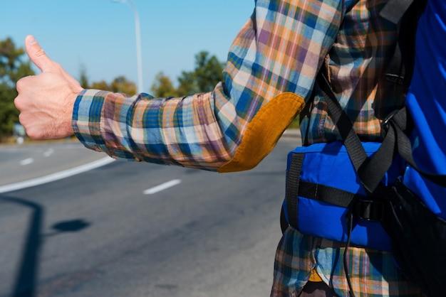 Nadszedł czas na przejażdżkę. zbliżenie: młody człowiek niosący plecak, wyciągając rękę z kciukiem do góry, stojąc na drodze