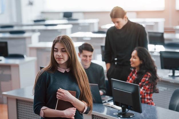 Nadszedł nowy dzień. grupa młodych ludzi w ubranie pracujących w nowoczesnym biurze