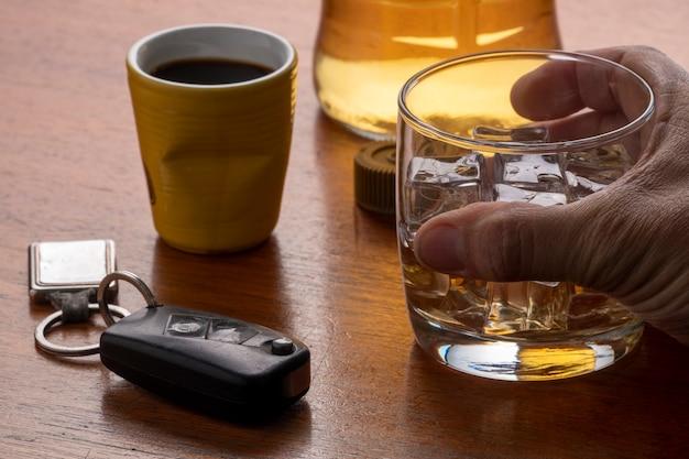 Nadużywanie alkoholu ze szklanką whisky z lodem i kluczykiem do samochodu na stole.
