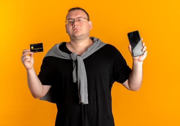 Nadwaga mężczyzna w okularach na sobie czarną koszulkę, trzymając smartfon pokazując kartę kredytową, patrząc pewnie na pomarańczowo