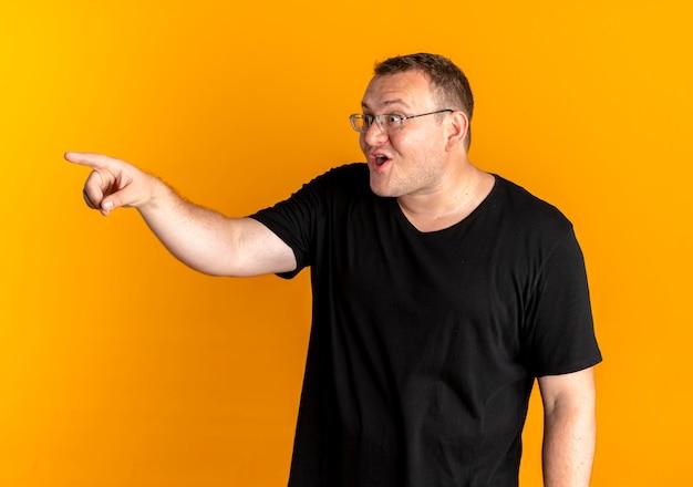 Nadwaga mężczyzna w okularach na sobie czarną koszulkę, wskazując palcem na coś szczęśliwego i podekscytowanego stojącego nad pomarańczową ścianą